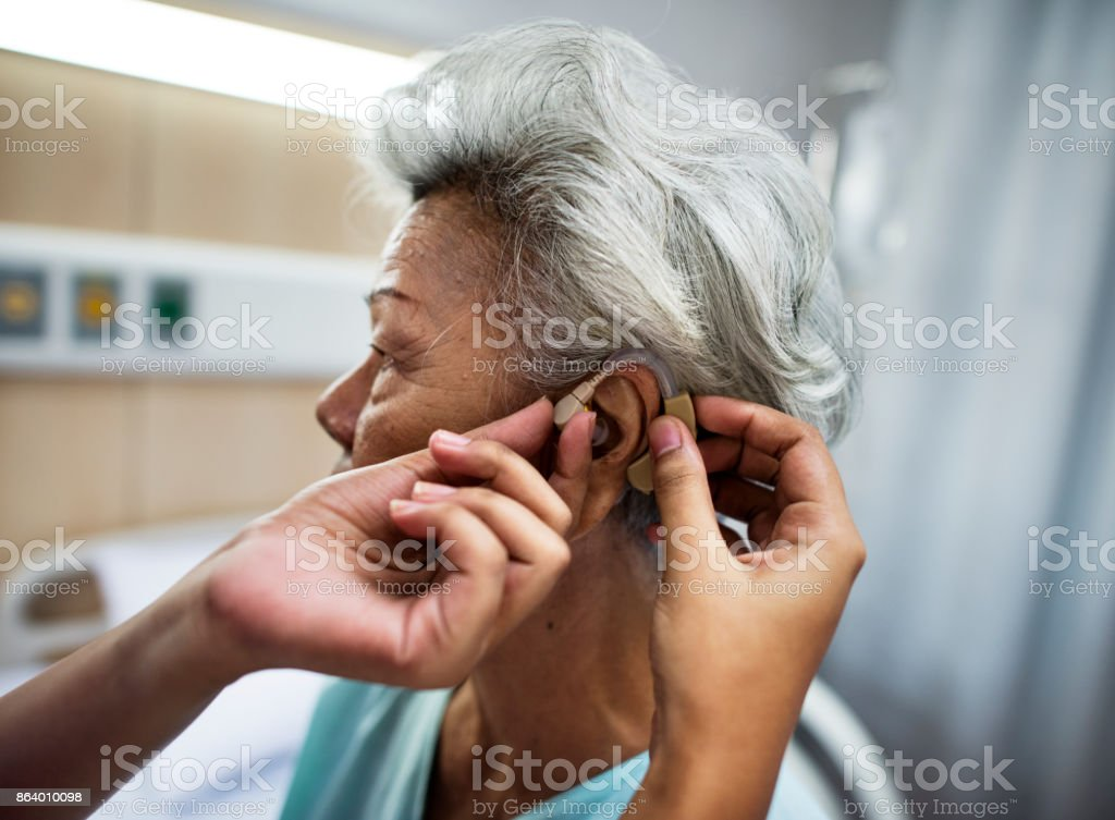 Asian old woman having her ears checked - foto stock