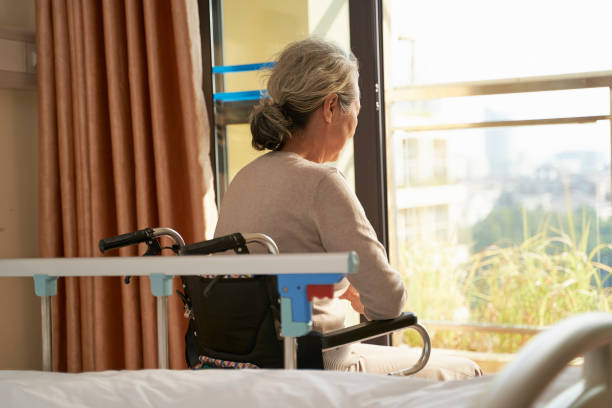 asian old woman sitting in wheel chair in front of window stock photo
