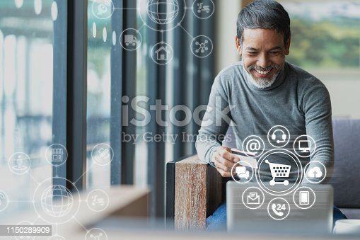 istock Asian or Hispanic man using Laptop and credit card payment shopping online with icon customer network connection on screen and connecting with omni channel system. Older man satisfied with CRM system 1150289909