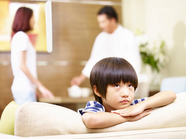 asian parents arguing while child neglected stock photo
