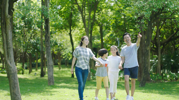 asian parents & kids walking outdoors on summer weekend & laughing - singapore nature stock photos and pictures