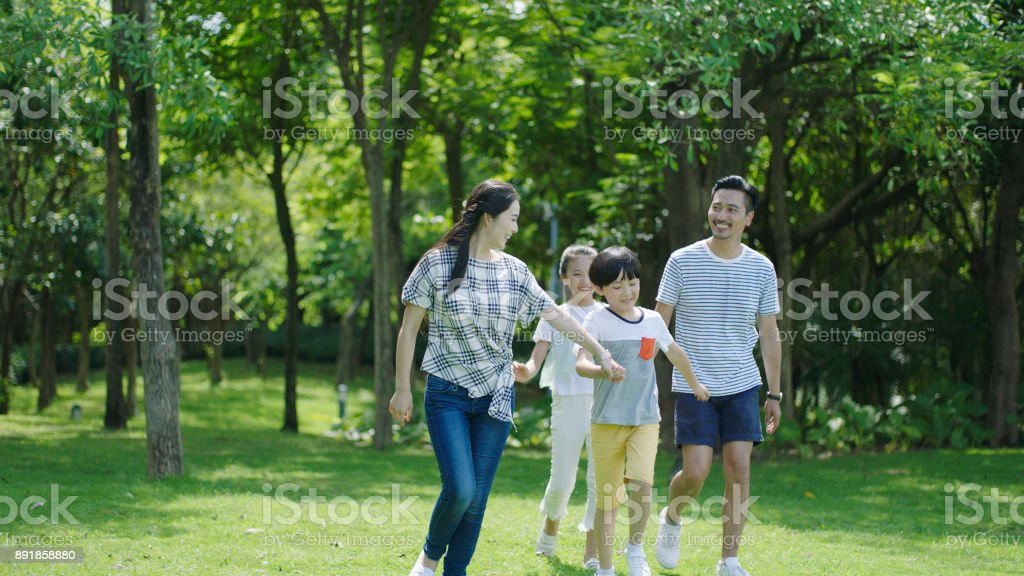 Asian parents & kids walking outdoors on summer weekend & laughing stock photo