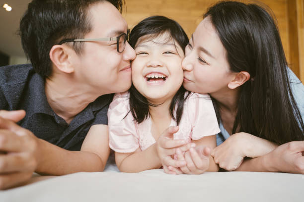 asian parents kissing their little daughter on both cheeks. family portrait. - ásia imagens e fotografias de stock