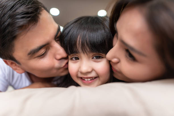 asian parents kissing their little daughter on both cheeks. - philippines girl stock photos and pictures