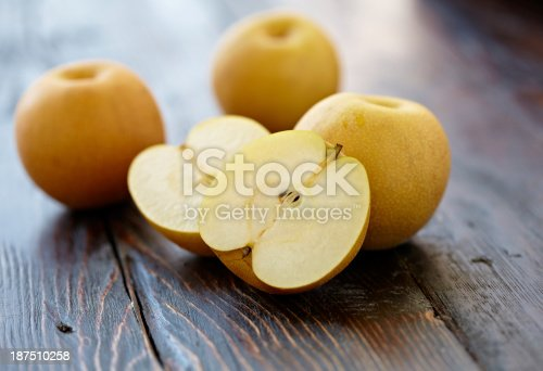 Asian pear sliced and three whole pears shot on wood background with shallow depth of focus.  Professionally shot, color corrected, exported 16 bit and retouched for maximum image quality.
