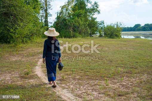 Asian women carrying transistor radio walk along the pathway in the meadow.