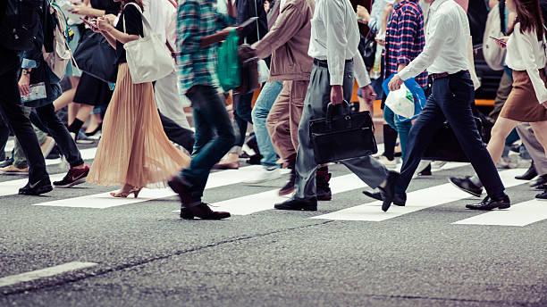 asiaten sind auf dem crosswalk - große personengruppe stock-fotos und bilder