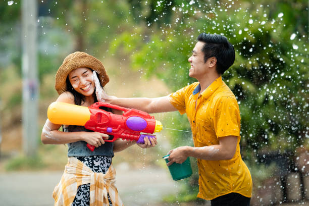 Asian people are using water guns play in the Songkran festival stock photo