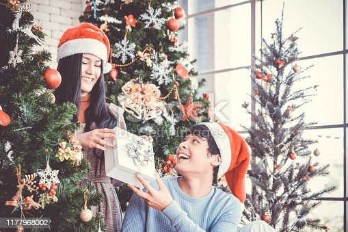 istock Asian people party celebrate christmas and new year eve in house. Man and woman giving gift box together 1177968002