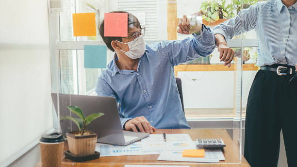 Asian People Successful Teamwork Business Wearing Medical Mask and Working. Work from Private Office Social Distancing among Coronavirus Outbreak Situation stock photo