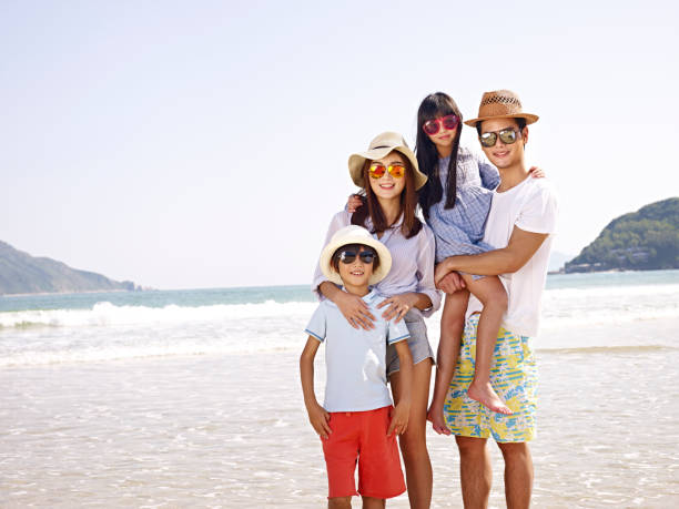 asian people taking a family photo on beach stock photo