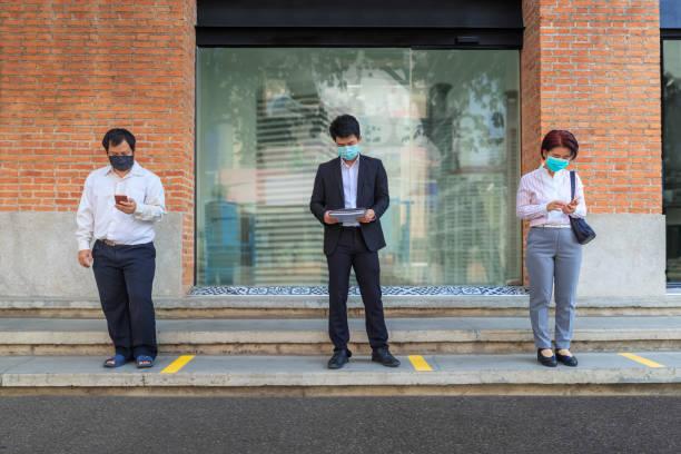 Las personas asiáticas que llevan máscara y mantienen el distanciamiento social para evitar la propagación de COVID-19 - foto de stock
