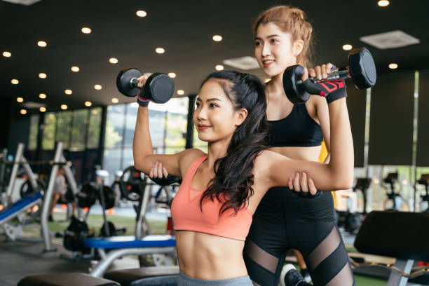 Asian personal trainer coaching a bodybuilding woman to perform the weightlifting exercise with dumbells in the fitness gym. stock photo
