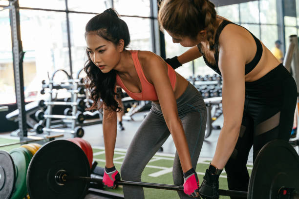 Asian personal trainer coaching a bodybuilding woman to perform the dead lifting exercise with barbell in the fitness gym. stock photo