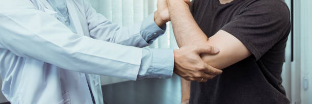 Asian physiotherapists check the elbows of patients who have undergone orthopedic rehabilitation. stock photo