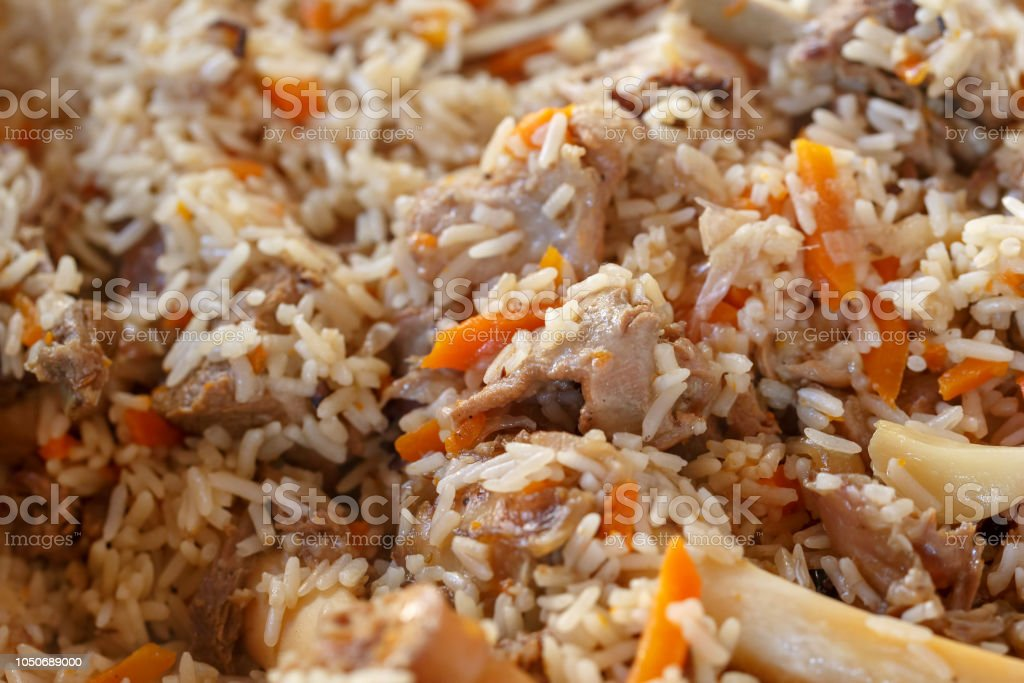Asian pilaf consisting of brown rice, pieces of stew lamb, carrots, garlic and other spices. Close-up stock photo