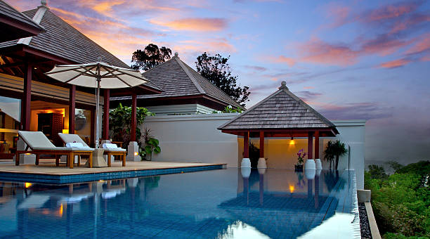 Asian Pool Villa A luxurious pool villa on a private infinity pool, all modern Asian style with a taste of zen design .. over looking the sea with the candy colors of the setting sun. luxury hotel room stock pictures, royalty-free photos & images