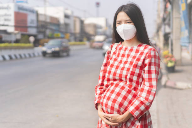 Asian pregnant Woman She is in the middle of the road Wear a PM2.5 dust mask. stock photo