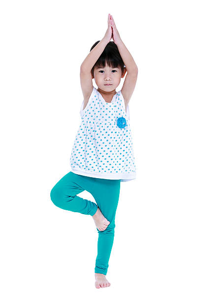 Asian pretty girl doing yoga exercises. Isolated on white background. stock photo