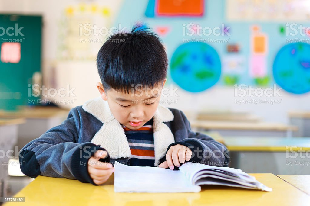 asian primary students read books in classroom stock photo
