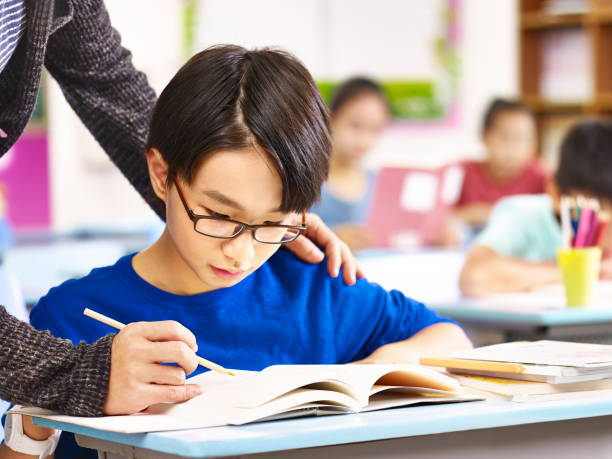 asian pupil getting help from teacher in class stock photo