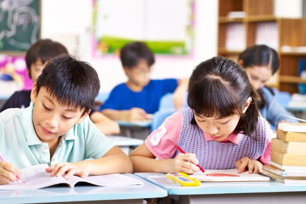 アジアの生徒が教室で勉強して - 小学校 ストックフォトと画像