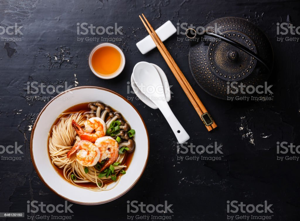 Asian Ramen noodles with broth in bowl serving size and Tea stock photo
