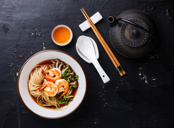 nouilles ramen asiatiques avec du bouillon dans un bol servant de taille et thé - cuisine asiatique photos et images de collection