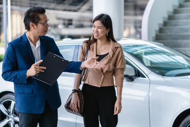 asiatische rezeptionistin begrüßt den kunden, um maintainance service-center für die überprüfung des autos im showroom zu besuchen - klavier verkaufen stock-fotos und bilder