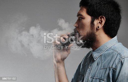 istock Asian Rocker man smoking electronic cigarette on grey background 586751132