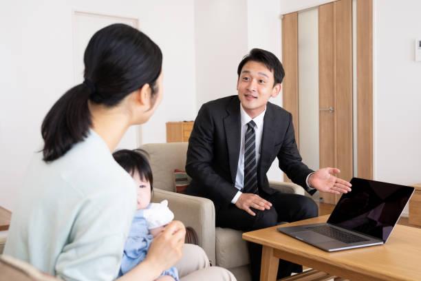 リビング ルームでアジアの営業担当者 - 営業 ストックフォトと画像