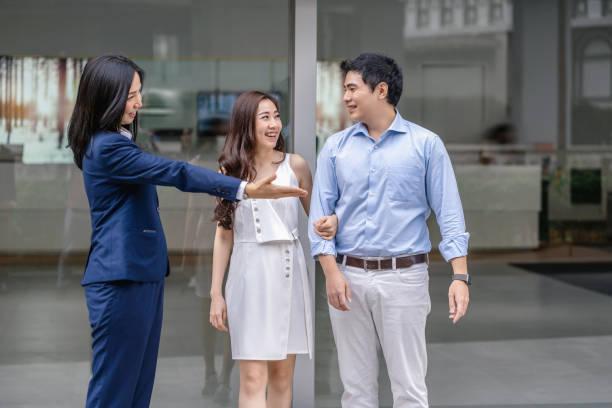asiatische verkäuferin begrüßt das paar kunden, um das auto vor dem showroom zu überprüfen, - klavier verkaufen stock-fotos und bilder