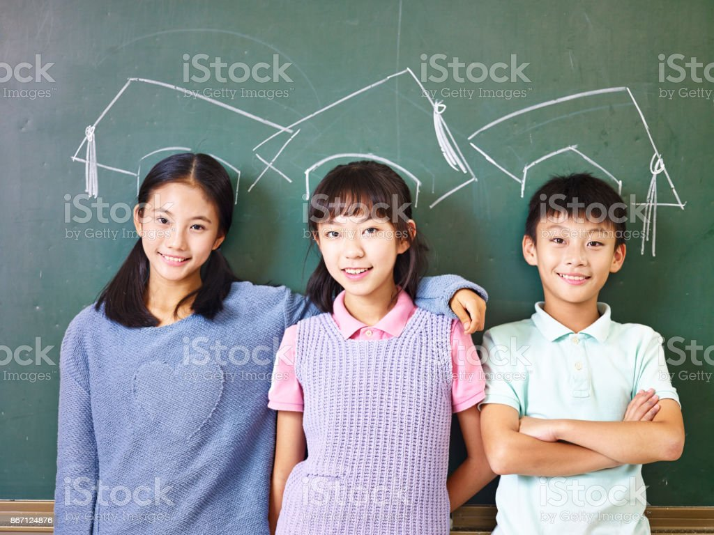 asian school children with chalk-drawn mortarboards stock photo