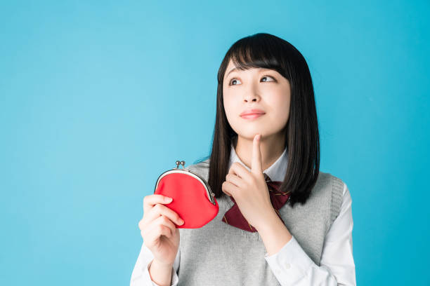 Asian school girl holding a coin purse. Asian school girl holding a coin purse. japanese school girl stock pictures, royalty-free photos & images
