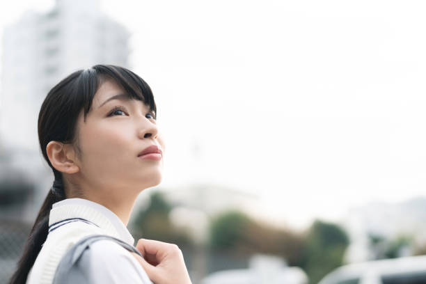 Asian school girl looking up to the sky. Asian school girl looking up to the sky. japanese school girl stock pictures, royalty-free photos & images