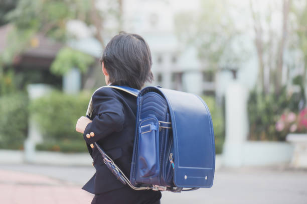 Asian school girl with pink backpack looking up stock photo