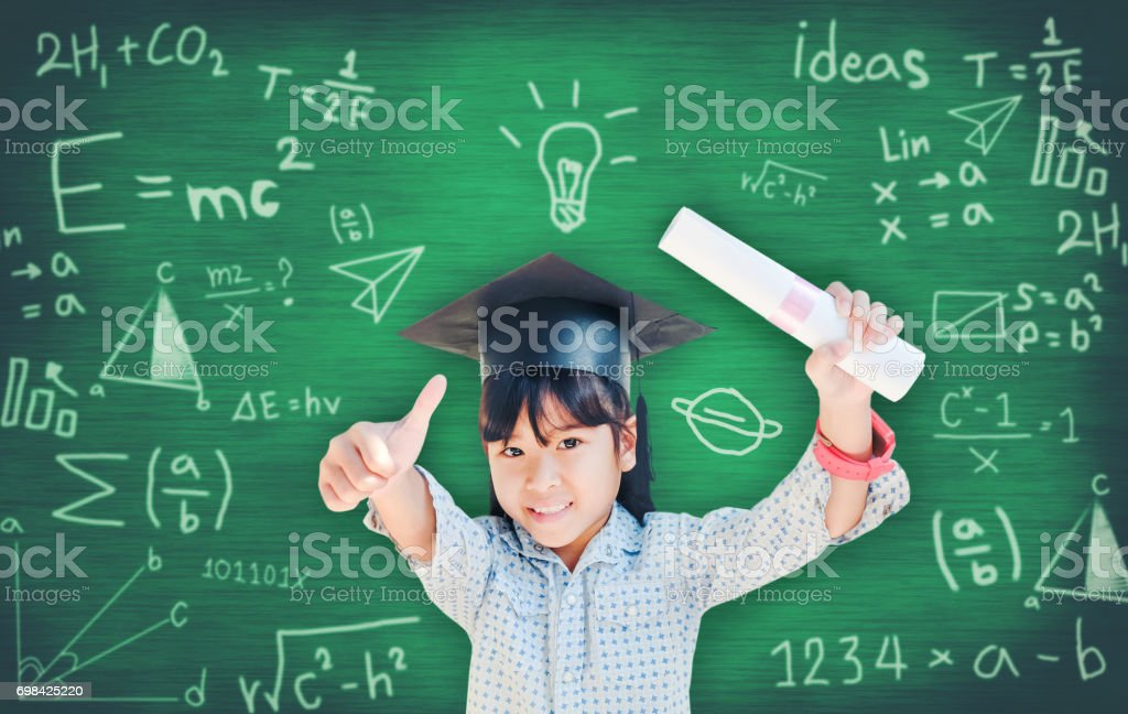 Asian school kid graduate in graduation cap for her success  over blackboard. stock photo