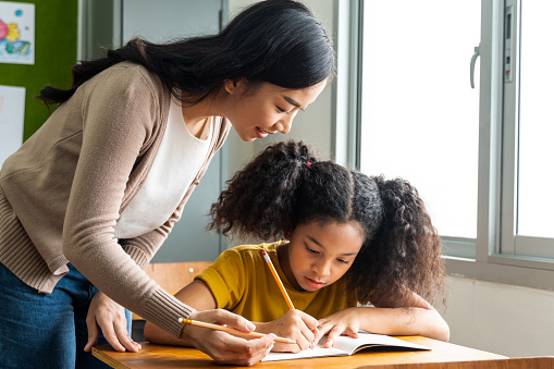 Asian school teacher assisting female student in classroom. Young woman working in school helping girl with her writing, education, support, care.