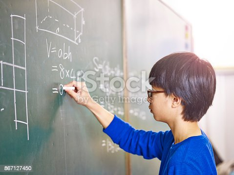 istock asian schoolboy solving geometry problem on blackboard 867127450