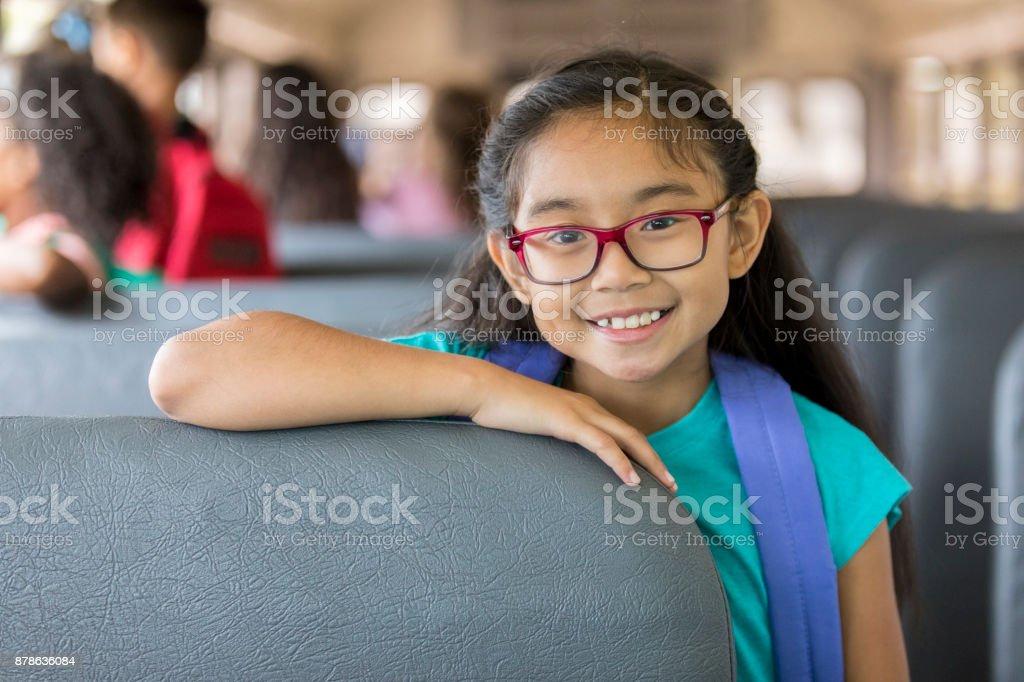 Asian schoolgirl riding on the school bus stock photo