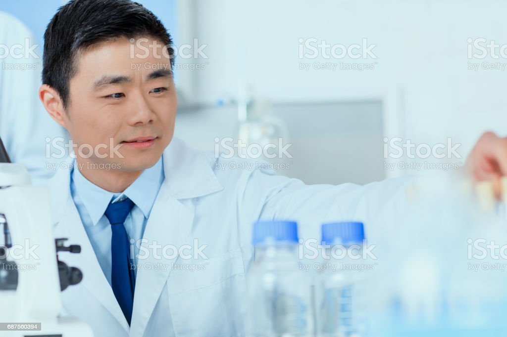 Asian scientist in white coat working in chemical laboratory stock photo