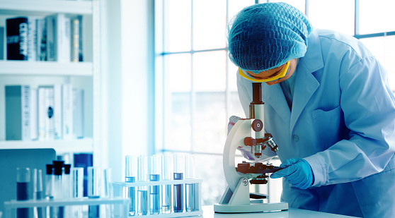 Asian scientist or doctors use microscopes to test for the coronavirus (COVID 19). Or a new flu virus to save human life In the lab Or hospital. Successful in researching the treatment of patients