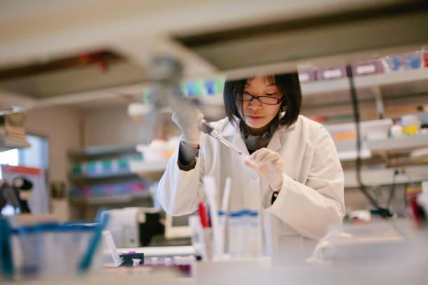 asian scientist pipetting at a biomedical laboratory - medical research stock photos and pictures