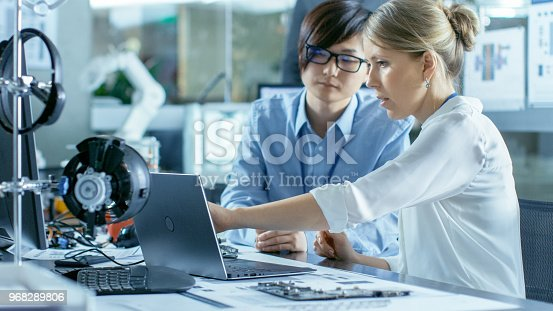 968289374istockphoto Asian Scientist Sitting at His Desk Consults Engineer about Sophisticated Coding and Programming. In the Background Computer Science Research Laboratory with Robotic Arm Model. 968289806