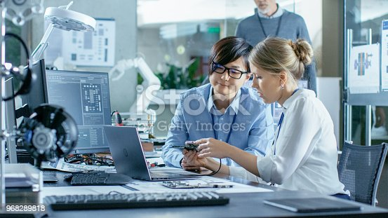 968289374istockphoto Asian Scientist Sitting at His Desk Consults Engineer They Connect Printed Circuit Board to a Laptop and Start Coding. In the Background Computer Science Research Laboratory with Robotic Arm Model. 968289818