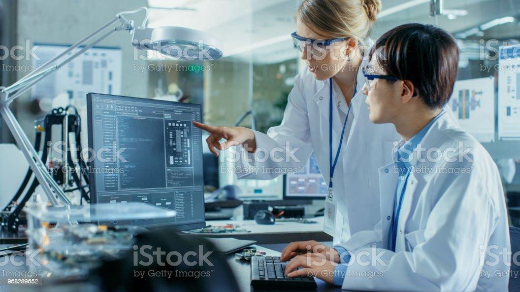 Asiatische Wissenschaftler sitzt an seinem Schreibtisch berät Oberingenieur über raffinierte Codierung und Programmierung. Im Hintergrund Computer Science Forschungslabor mit Roboterarm Modell. – Foto