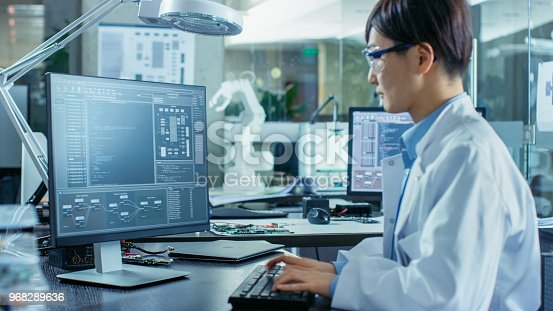 istock Asian Scientist Sitting at His Desk Doing Sophisticated Coding and Programming on His Desktop Computer. In the Background Computer Science Research Laboratory with Robotic Arm Model. 968289636