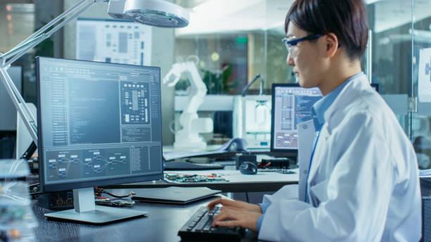 アジアの科学者は高度なコーディングと彼のデスクトップ コンピューターでプログラミングを行う彼の机に座って。ロボット アームのモデルと背景コンピューター科学研究所。 ストックフォト