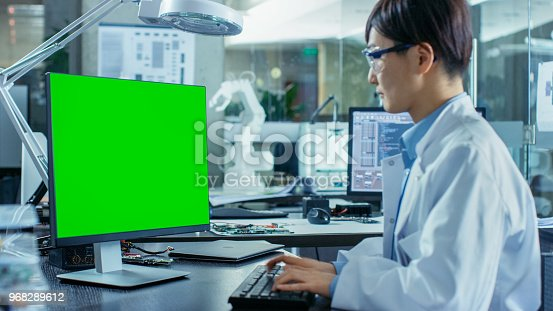 968289374istockphoto Asian Scientist Sitting at His Desk Works on a Personal Computer with Mock-up Green Screen. In the Background Computer Science Research Laboratory with Robotic Arm Model. 968289612