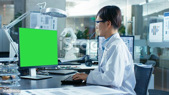 968289374istockphoto Asian Scientist Sitting at His Desk Works on a Personal Computer with Mock-up Green Screen. In the Background Computer Science Research Laboratory with Robotic Arm Model. 968289620